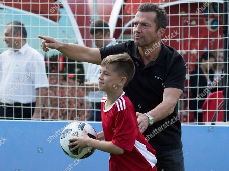 German soccer player Lothar Matthaus talks to a member of one of the teams, prior to a friendly soccer match between two children teams and FIFA legends at Football Park in Red Square during the 2018 soccer World Cup in Moscow, Russia