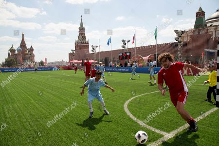 Former player of the Spanish national soccer team Carles Puyol, right, takes part in a friendly soccer match between two children teams and FIFA legends at Football Park in Red Square during the 2018 soccer World Cup in Moscow, Russia