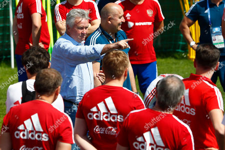 Stock Image of Former Russian national soccer coach Guus Hiddink, center, talks to players besides Russia head coach Stanislav Cherchesov during the official training session of the Russian team prior to the round of 16 match between Russia and Spain at the 2018 soccer World Cup at the Federal Sports Centre Novogorsk, near Moscow, Russia
