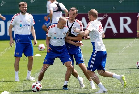 Russia's Artyom Dzyuba, center, challenges for the ball with his teammates Igor Smolnikov, left, and Yuri Gazinsky during the official training session of the Russian team prior to the round of 16 match between Russia and Spain at the 2018 soccer World Cup at the Federal Sports Centre Novogorsk, near Moscow, Russia