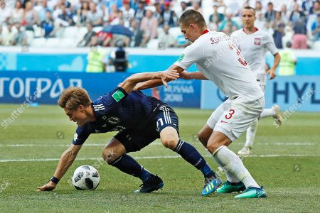 Poland's Artur Jedrzejczyk, right, pushes Japan's Gotoku Sakai during the group H match between Japan and Poland at the 2018 soccer World Cup at the Volgograd Arena in Volgograd, Russia