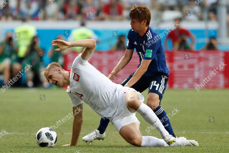 Poland's Lukasz Teodorczyk, left, and Japan's Takashi Inui vie for the ball during the group H match between Japan and Poland at the 2018 soccer World Cup at the Volgograd Arena in Volgograd, Russia