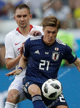 Poland's Artur Jedrzejczyk, background, defends against Japan's Gotoku Sakai during the group H match between Japan and Poland at the 2018 soccer World Cup at the Volgograd Arena in Volgograd, Russia
