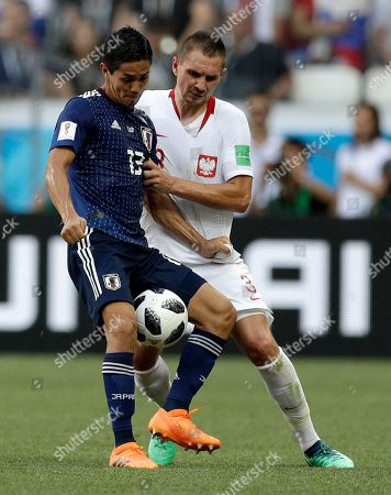 Japan's Yoshinori Muto, left, and Poland's Artur Jedrzejczyk fight for the ball during the group H match between Japan and Poland at the 2018 soccer World Cup at the Volgograd Arena in Volgograd, Russia
