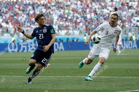 Japan's Gotoku Sakai, left, stops the ball next to Poland's Artur Jedrzejczyk during the group H match between Japan and Poland at the 2018 soccer World Cup at the Volgograd Arena in Volgograd, Russia