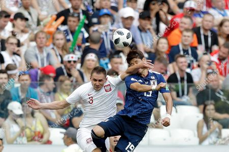 Japan's Hiroki Sakai, right, and Poland's Artur Jedrzejczyk jump for the ball during the group H match between Japan and Poland at the 2018 soccer World Cup at the Volgograd Arena in Volgograd, Russia
