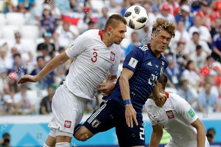 Japan's Gotoku Sakai, right, and Poland's Artur Jedrzejczyk jump for the ball during the group H match between Japan and Poland at the 2018 soccer World Cup at the Volgograd Arena in Volgograd, Russia