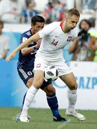 Poland's Lukasz Teodorczyk, right, controls the ball as Japan's Tomoaki Makino tries to stop him during the group H match between Japan and Poland at the 2018 soccer World Cup at the Volgograd Arena in Volgograd, Russia