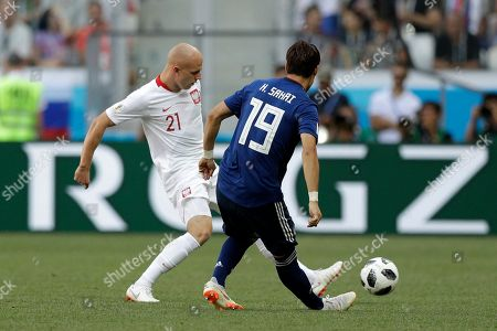 Japan's Hiroki Sakai, right, defends against Poland's Rafal Kurzawa during the group H match between Japan and Poland at the 2018 soccer World Cup at the Volgograd Arena in Volgograd, Russia