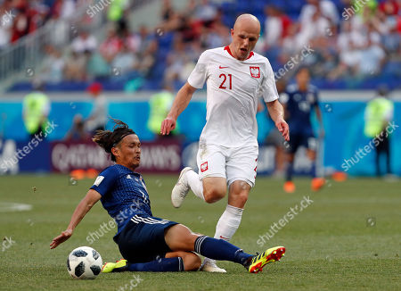 Japan's Takashi Usami, left, challenges Poland's Rafal Kurzawa during the group H match between Japan and Poland at the 2018 soccer World Cup at the Volgograd Arena in Volgograd, Russia