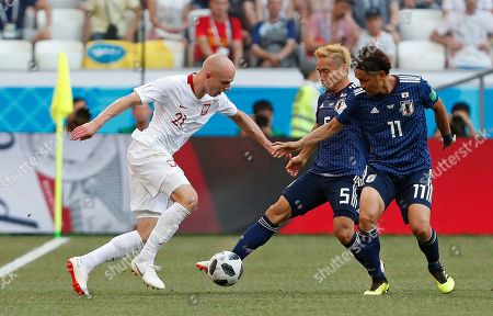 Poland's Rafal Kurzawa, left, is challenged by Japan's Takashi Usami, right, and Yuto Nagatomo during the group H match between Japan and Poland at the 2018 soccer World Cup at the Volgograd Arena in Volgograd, Russia