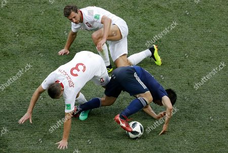Japan's Shinji Okazaki vies for the ball with Poland's Artur Jedrzejczyk, left, during the group H match between Japan and Poland at the 2018 soccer World Cup at the Volgograd Arena in Volgograd, Russia