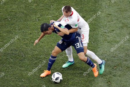 Japan's Yoshinori Muto pulls the shirt of Poland's Artur Jedrzejczyk, right, during the group H match between Japan and Poland at the 2018 soccer World Cup at the Volgograd Arena in Volgograd, Russia