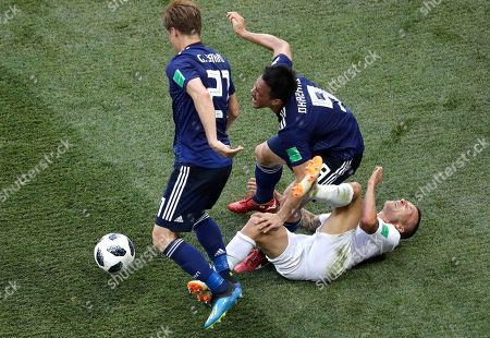 Poland's Jacek Goralski, on the ground, tackles both Japan's Gotoku Sakai, left, and Shinji Okazaki during the group H match between Japan and Poland at the 2018 soccer World Cup at the Volgograd Arena in Volgograd, Russia