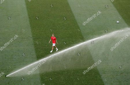 Poland's Lukasz Teodorczyk walks by a water sprinkler as the pitch is watered just before the start of the group H match between Japan and Poland at the 2018 soccer World Cup at the Volgograd Arena in Volgograd, Russia