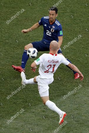 Japan's Maya Yoshida vies for the ball with Poland's Rafal Kurzawa, foreground, during the group H match between Japan and Poland at the 2018 soccer World Cup at the Volgograd Arena in Volgograd, Russia