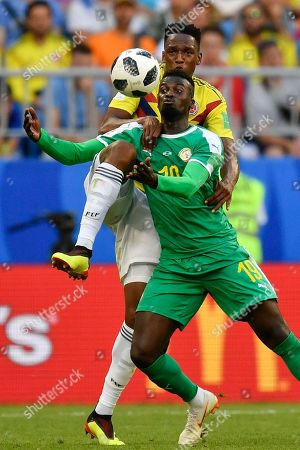 Senegal's Mbaye Niang, bottom, vies for the ball with Colombia's Oscar Murillo, top, during the group H match between Senegal and Colombia, at the 2018 soccer World Cup in the Samara Arena in Samara, Russia