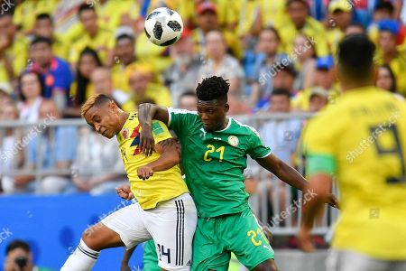 Colombia's Luis Muriel, left, jumps for the ball with Senegal's Lamine Gassama during the group H match between Senegal and Colombia, at the 2018 soccer World Cup in the Samara Arena in Samara, Russia