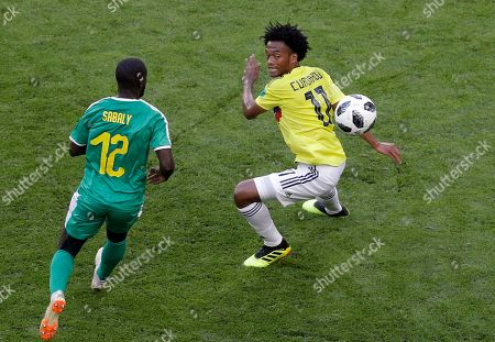 Colombia's Juan Cuadrado, right, vies for the ball with Senegal's Youssouf Sabaly during the group H match between Senegal and Colombia, at the 2018 soccer World Cup in the Samara Arena in Samara, Russia