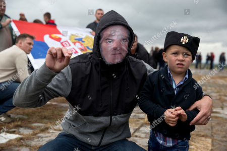 A Serb man with a child wears a face mask depicting Serbian war criminal Ratko Mladic as he participates in a ceremony commemorating a medieval battle with invading Ottoman forces in 1389 at Gazimestan, Kosovo, . Hundreds of Serbs gathered on Thursday to mark the 629th anniversary of the battle where the Serbian army was defeated by the Ottoman Empire
