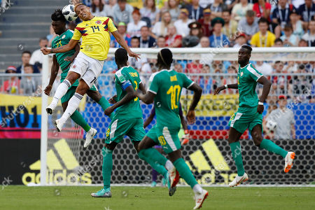 Senegal's Lamine Gassama, left, and Colombia's Luis Muriel challenge for the ball during the group H match between Senegal and Colombia, at the 2018 soccer World Cup in the Samara Arena in Samara, Russia