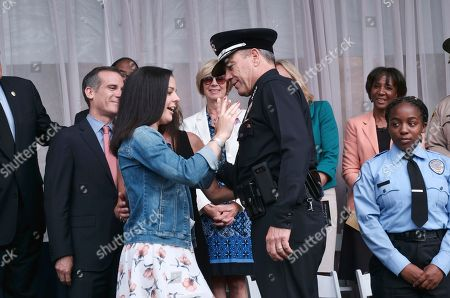 Michel Moore and daughter Haley. Michel Moore has his police badge pinned on his shirt by his daughter Haley, after he was sworn in as the new Los Angeles Chief at the police academy on. Moore replaces Charlie Beck, who retired Wednesday, June 27, 2018, after more than 40 years with the LAPD