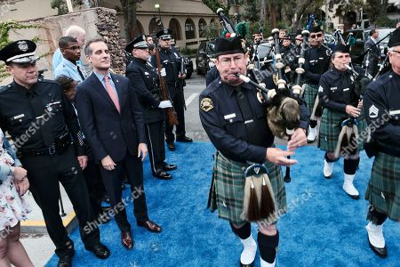 Michel Moore, Eric Garcetti. Michel Moore, left and Los Angeles Mayor Eric Garcetti, second from left, watch the Emerald Society Pipes & Drums arrive before Moore was sworn in as the new Los Angeles Chief at the police academy, . Moore replaces Charlie Beck, who retired Wednesday, June 27, 2018, after more than 40 years with the LAPD. Beck became the chief in 2009
