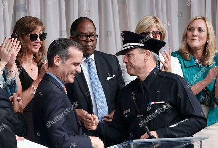 Eric Garcetti, Michel Moore. Los Angeles Mayor Eric Garcetti, left, congratulates longtime Police Department veteran Michel Moore after Moore was sworn in as the city's new police chief, at the police academy in Los Angeles. Moore replaces Charlie Beck, who retired Wednesday, June 27, 2018, after more than 40 years with the LAPD. Beck became the chief in 2009
