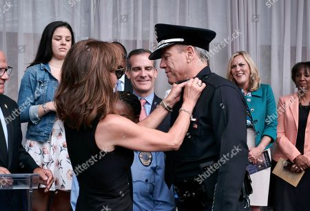 Michel Moore. Los Angeles Mayor Eric Garcetti, center looks on as Michel Moore gets his stars pinned on his shirt by his wife Cindy after being sworn in as the new Los Angeles Chief at the police academy on. Moore replaces Charlie Beck, who retired Wednesday, June 27, 2018, after more than 40 years with the LAPD. Beck became the chief in 2009