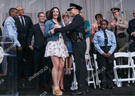 Michel Moore and daughter Haley. Haley Moore, center, reacts after pinning her father's police badge on him after Michel Moore was sworn in as Los Angeles Police Chief at the police academy on . Moore replaces Charlie Beck, who retired Wednesday, June 27, 2018, after more than 40 years with the LAPD. Beck became the chief in 2009