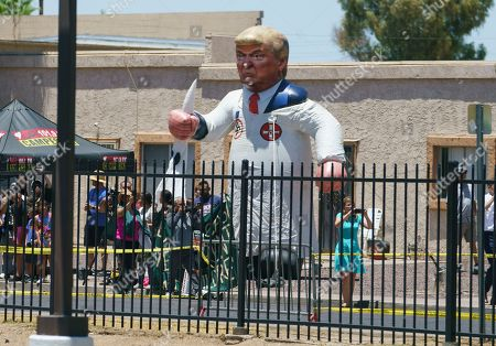 Protesters place a large inflatable balloon in the likeness of President Donald Trump dressed in a Ku Klux Klan sheet across the street from Southwest Key Campbell, a shelter for children that have been separated from their parents, in Phoenix, Ariz., during a visit by first lady Melania Trump