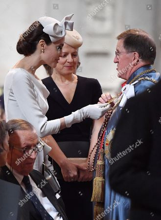 Actress and director Angelina Jolie looks at a part of the formal robes of Lord Robertson of Port Ellen after arriving ahead of the Order Of St George 200th Anniversary Service at St Paul's Cathedral.