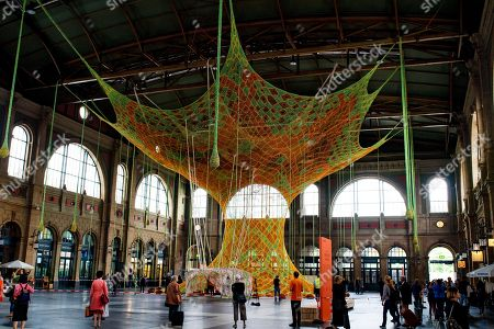 The art installation 'GaiaMotherTree' of Brazilian artist Ernesto Neto is displayed at the Zurich Central Station, in Zurich, Switzerland, 29 June 2018. The museum Fondation Beyeler presents the monumental artwork, a colorful, tree-like sculpture made of cotton ribbons that spread up to the 20-meter-high ceiling of the station from 30 June to 29 July.