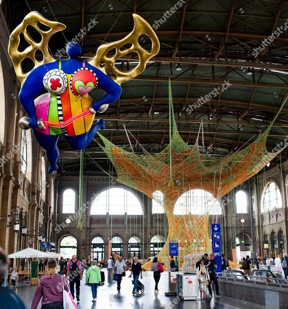 The sculpture 'L'ange protecteur' by French-Swiss artist Niki de Saint Phalle (front) and the art installation 'GaiaMotherTree' of Brazilian artist Ernesto Neto are displayed at the Zurich Central Station, in Zurich, Switzerland, 29 June 2018. The museum Fondation Beyeler presents the monumental artwork, a colorful, tree-like sculpture made of cotton ribbons that spread up to the 20-meter-high ceiling of the station from 30 June to 29 July.