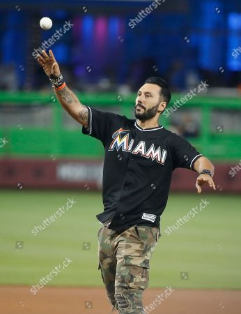 Grammy-Winning DJ and producer Cedric Gervais throws out a ceremonial first pitch before the start of a baseball game between the Miami Marlins and the New York Mets, in Miami