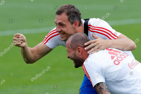 Russia's Artyom Dzyuba, left, and Russia's Fyodor Kudryashov laugh during Russia's official training ahead of the round of 16 match between Russia and Spain at the 2018 soccer World Cup at the Federal Sports Centre Novogorsk, near Moscow, Russia