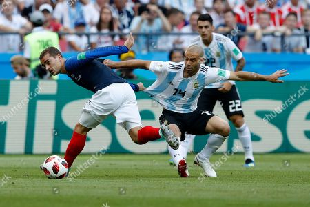 France's Antoine Griezmann, left, and Argentina's Javier Mascherano challenge for the ball during the round of 16 match between France and Argentina, at the 2018 soccer World Cup at the Kazan Arena in Kazan, Russia