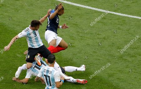 France's Kylian Mbappe is fouled by Argentina's Javier Mascherano, bottom, and Nicolas Tagliafico during the round of 16 match between France and Argentina, at the 2018 soccer World Cup at the Kazan Arena in Kazan, Russia