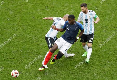 France's Paul Pogba, front, falls beside Argentina's Javier Mascherano, left, and Lionel Messi during the round of 16 match between France and Argentina, at the 2018 soccer World Cup at the Kazan Arena in Kazan, Russia