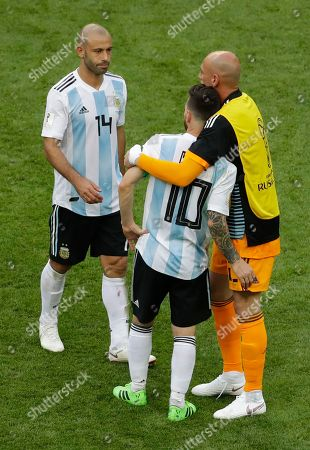 Argentina's Lionel Messi, center, is comforted by Javier Mascherano, left, after Argentina was eliminated during the round of 16 match between France and Argentina, at the 2018 soccer World Cup at the Kazan Arena in Kazan, Russia