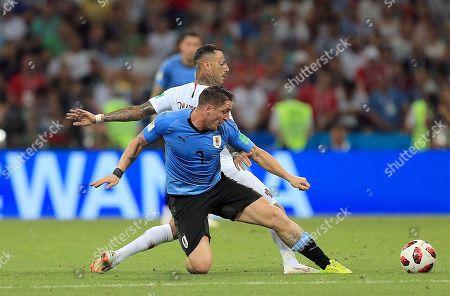 Cristian Rodriguez of Uruguay tackles Ricardo Quaresma of Portugal