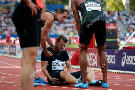 Christophe Lemaitre of France, center, suffers an injury during the Men's 100 meters B race competition at the IAAF Diamond League athletics meeting at Charlety Stadium, in Paris, France