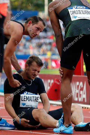 Christophe Lemaitre of France, center, suffers an injury during the Men's 100 meters B racecompetition at the IAAF Diamond League athletics meeting at Charlety Stadium, in Paris, France