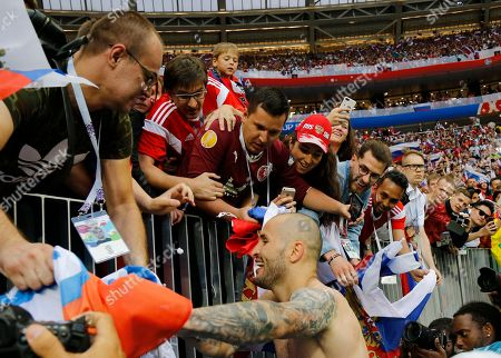 Russia's Fyodor Kudryashov celebrates with fans after winning the the round of 16 match between Spain and Russia at the 2018 soccer World Cup at the Luzhniki Stadium in Moscow, Russia