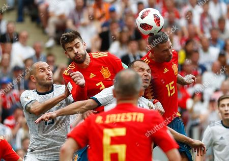 Russia's Fyodor Kudryashov, Spain's Gerard Pique, Russia's Sergei Ignashevich and Spain's Sergio Ramos, from left, go for a header during the round of 16 match between Spain and Russia at the 2018 soccer World Cup at the Luzhniki Stadium in Moscow, Russia