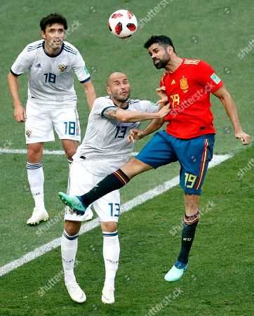 Spain's Diego Costa, right, and Russia's Fyodor Kudryashov, center, go for a header during the round of 16 match between Spain and Russia at the 2018 soccer World Cup at the Luzhniki Stadium in Moscow, Russia