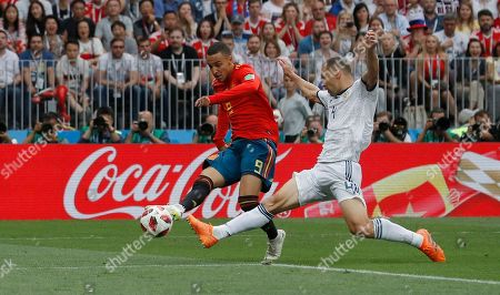 Spain's Rodrigo, left shoots at goal as Russia's Sergei Ignashevich defends during the round of 16 match between Spain and Russia at the 2018 soccer World Cup at the Luzhniki Stadium in Moscow, Russia