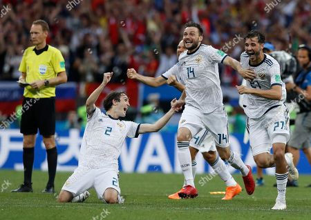 Stock Photo of Russia's Mario Fernandes, left Russia's Vladimir Granat, centre, and Russia's Mario Fernandes react as Russia defeats Spain in a penalty shoot out during the round of 16 match between Spain and Russia at the 2018 soccer World Cup at the Luzhniki Stadium in Moscow, Russia