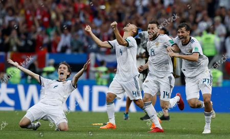 Russia's Mario Fernandes, left Russia's Sergei Ignashevich, Russia's Vladimir Granat, and Russia's Mario Fernandes react as Russia defeats Spain by winning a penalty shoot out in the round of 16 match between Spain and Russia at the 2018 soccer World Cup at the Luzhniki Stadium in Moscow, Russia