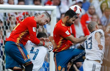 Spain's Sergio Ramos, left, and Diego Costa, center right, challenges for the ball with Russia's Sergei Ignashevich, center left, and Fyodor Kudryashov during the round of 16 match between Spain and Russia at the 2018 soccer World Cup at the Luzhniki Stadium in Moscow, Russia